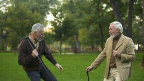 Męscy emeryci tanczy parka z chodzącymi kijami, przyjaźń humor, mieć zabawę zbiory wideo