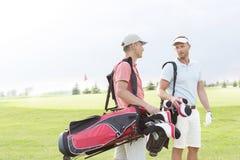 Męscy golfiści komunikuje przy polem golfowym przeciw jasnemu niebu Zdjęcia Royalty Free