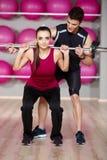 Męscy Gym instruktora kobiety przewożenia Pomaga ciężary Zdjęcia Stock