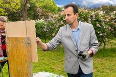 Męscy i żeńscy artyści maluje arcydzieło w parku Obraz Stock