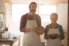 Męscy i żeńscy garncarki mienia earthenware garnki Zdjęcia Stock