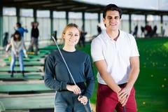 Męscy i żeńscy golfiści przygotowywający dla drużynowej sztuki przy polem golfowym Obrazy Stock