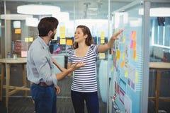 Męscy i żeńscy kierownictwa dyskutuje nad whiteboard zdjęcia stock