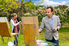 Męscy i żeńscy malarzi pracuje outdoors Fotografia Stock