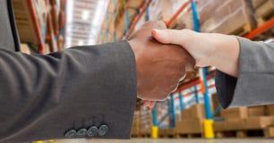 Męscy i żeńscy partnery biznesowi trząść ręki w magazynie Zdjęcia Royalty Free