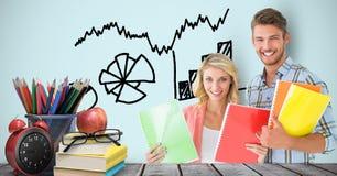 Męscy i żeńscy ucznie trzyma książki przy biurkiem przeciw grafika Fotografia Stock