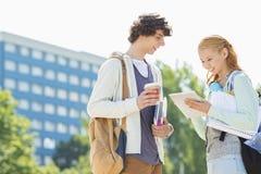 Męscy i żeńscy ucznie używa cyfrową pastylkę przy szkoła wyższa kampusem Zdjęcie Stock