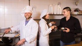 Męscy kelnera mienia naczynia przy kuchnią Fotografia Royalty Free