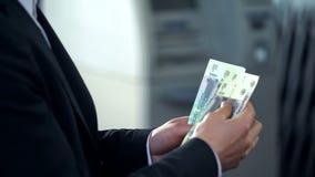 Męscy odliczający gruzy wycofujący od ATM, dobra usługa, podróż służbowa Rosja fotografia stock