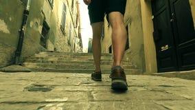 Męscy podróżniczy ` s cieki, tylny widok Chodzić wzdłuż antycznej Mediterranian miasta ulicy zbiory wideo