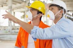 Męscy pracownicy budowlani ma dyskusję przy miejscem Zdjęcie Stock