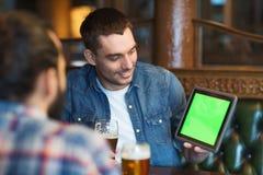 Męscy przyjaciele pije piwo przy barem z pastylka komputerem osobistym zdjęcie royalty free