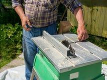Męscy ręk cięcia z kurendą zobaczyli kawałek deska na słonecznym dniu stonowany Obrazy Stock