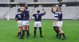 Męscy rugby gracze świętuje cel w ziemi przy stadium 4k zbiory