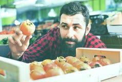Męscy sprzedawca ofiary persimmons w sklepu spożywczego sklepie Obrazy Stock