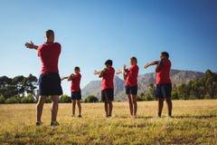 Męscy trenera instruowania dzieciaki podczas gdy ćwiczący w obóz dla rekrutów Obraz Stock