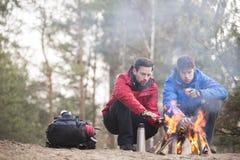 Męscy wycieczkowicze grże ręki przy ogniskiem w lesie Obraz Royalty Free