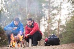 Męscy wycieczkowicze grże ręki przy ogniskiem w lesie Zdjęcie Stock