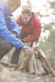 Męscy wycieczkowicze zaświeca ognisko w lesie Obraz Royalty Free