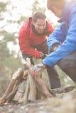 Męscy wycieczkowicze zaświeca ognisko w lesie Fotografia Royalty Free