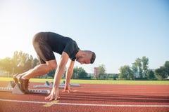 Męska atleta biega ślad na zaczyna pozyci przy atletyka Zdjęcie Royalty Free