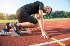 Męska atleta biega ślad na zaczyna pozyci przy atletyka Obraz Stock