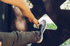 Męska atleta w bieg sportach kuje pozycji rozciągliwość jego noga na sporta polu z metal drabiną rozciągliwość wręczają stopa zdjęcie stock
