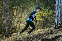Męska atleta wspina się stromego wzgórze w drewnach Obrazy Stock