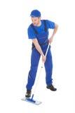 Męska czeladna mopping podłoga nad białym tłem Obraz Royalty Free