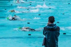 Męska dopłynięcie trenera pozycja pływackim basenem w podeszczowym wa Zdjęcia Royalty Free