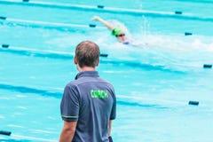 Męska dopłynięcie trenera pozycja pływackim basenem w podeszczowym wa Zdjęcie Royalty Free