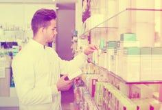 Męska farmaceuta jest ubranym białą żakiet pozycję w aptece Obrazy Royalty Free