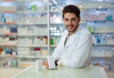 Męska farmaceuta wydaje medycynę trzyma pudełko ta Zdjęcia Stock