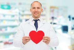 Męska farmaceuta z sercem przy apteką Fotografia Royalty Free