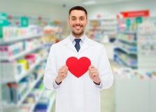 Męska farmaceuta z sercem przy apteką Zdjęcia Stock