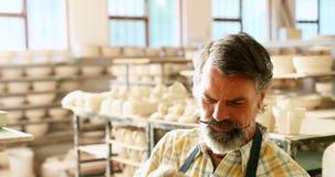 Męska garncarka sprawdza ceramiczną sztuki pracę 4k zdjęcie wideo