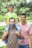 Męska homoseksualna para z przybranym synem ma zabawę w parku zdjęcie stock