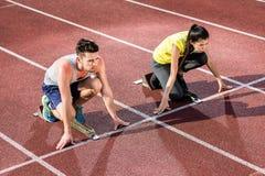 Męska i żeńska atleta w zaczyna pozyci przy zaczyna blokiem Obrazy Stock