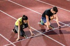 Męska i żeńska atleta w zaczyna pozyci przy zaczyna blokiem Zdjęcia Royalty Free