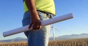 Męska inżynier pozycja z projektem w wiatrowym gospodarstwie rolnym 4k zbiory wideo