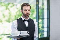 Męska kelnera mienia taca z filiżankami Zdjęcia Stock