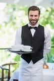 Męska kelnera mienia taca z filiżankami Fotografia Stock