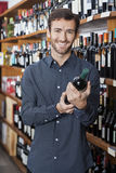 Męska klienta mienia wina butelka półkami Obraz Stock