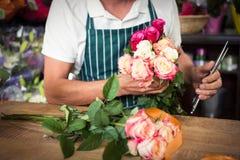 Męska kwiaciarnia trzyma wiązkę róże i strzyżenia Fotografia Stock