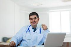 Męska lekarka z filiżanką kawy przy komputerem Obraz Royalty Free