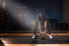Męska mięśniowa atleta ćwiczy z kettlebell obraz stock
