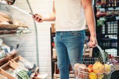 Męska nabywca z koszem i telefonem komórkowym w rękach fotografia stock