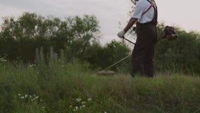 Męska ogrodniczka pracuje z fachowym wyposażeniem w ogródzie zbiory wideo