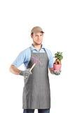 Męska ogrodniczka trzyma mattock i rośliny Obrazy Stock
