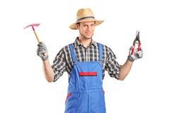 Męska ogrodniczka trzyma pracujących narzędzia Fotografia Stock